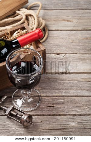Red wine bottle and glass on wooden table. View with copy space