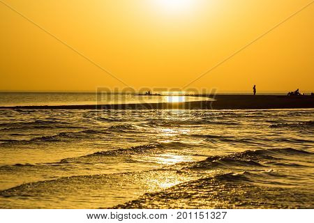 Picturesque orange sunset over the sand spit in the sea on the summer evening