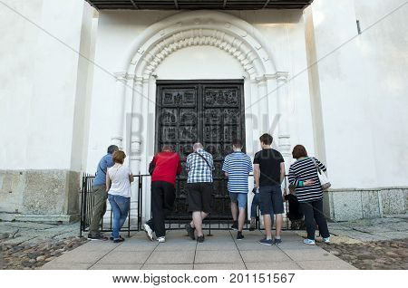few people standing at the metal doors of the Orthodox Church of entry into Jerusalem territory of the Novgorod Kremlin