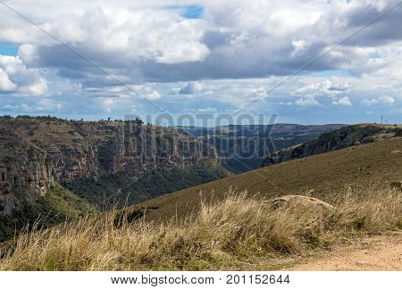 Dry Grassland Gorge Mountains And Valleys Against  Cloudy Sky