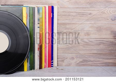 Vinyl records and headphones on table. Vintage vinyl disk
