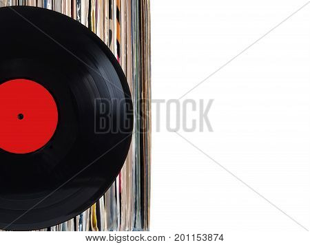 Black record with red label and pile of many close standing vinyl records in old color covers on left side on photo over white background studio shot front view closeup