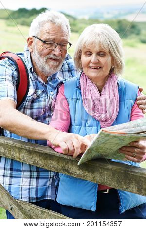 Senior Couple Hiking In Countryside With Map
