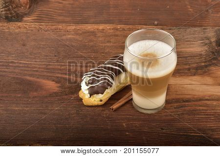 Latte macchiato and éclair. A cup of latte coffee top view on old wood background.