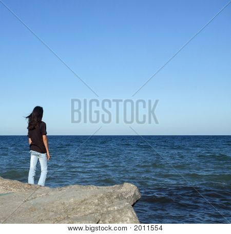 Girl On Rock Looks Out At Water