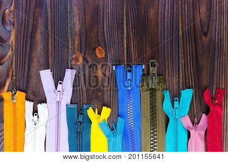 Multicolored zippers are laid out on a wooden table