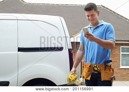 Electrician Outside House Checking Message On Mobile Phone