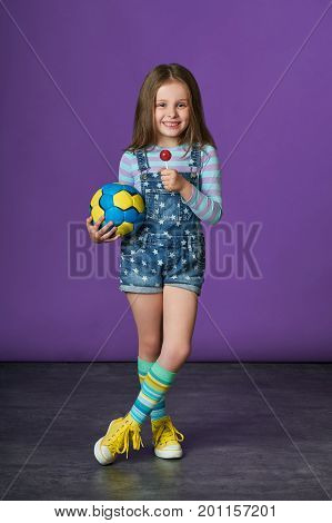 beautiful little girl eating candy. children's sports fashion