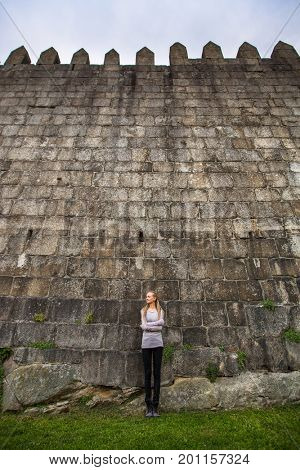 Young woman standing near the a huge medieval stone wall.