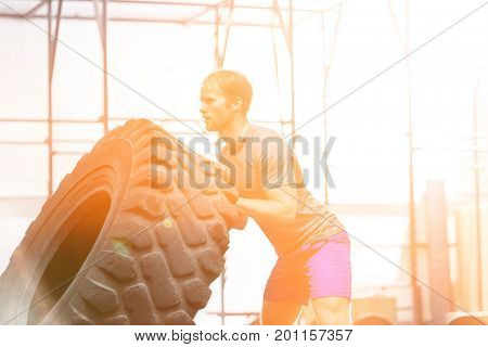 Side view of dedicated man flipping tire in crossfit gym