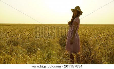pretty girl in the dress is walking across the field. Freedom concept