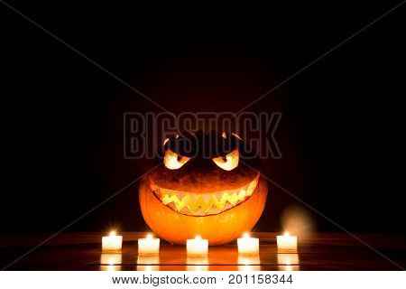 Candlelight halloween pumpkin smile with burning fire eyes mouth. Big spooky helloween symbol has a glowing mad face and smiling with sharp teeth and bad look. Black orange nightmare of October 31st.