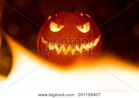 Fire flames halloween pumpkin smile with hot burning eyes mouth. Big spooky helloween symbol has a glowing mad face and smiling with sharp teeth and bad look. Black orange nightmare of October 31st.