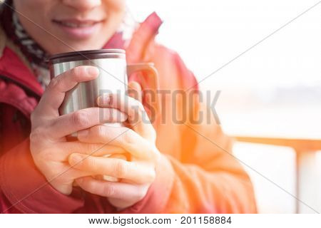 Midsection of man holding insulated drink container during winter