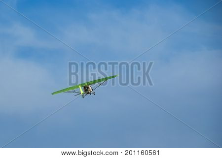 A flying hang-glider with a motor on the background of a blue sky a view from below