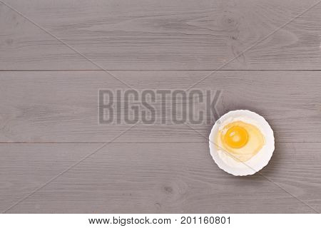 Eggs on a wooden table top view. Natural eco food. Gray, wooden table top view. On the table are the food for cooking. Healthy food. Dietetic foods. Delicious breakfast. Traditional food.