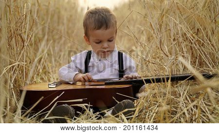 Little boy sitting in a golden wheat field and playing the guitar