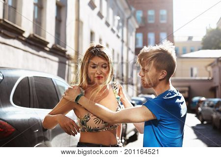 Please don't leave me. Unhappy remorseful young bearded man standing on city street holding hands on his girlfriend's shoulders asking her to forgive him. Harassment quarrel fight and disagreement poster