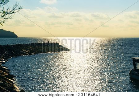 Sunset over a bay showing the blue water and the golden sunlight. There is a rocky outcrop stretching into the sea
