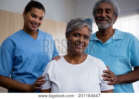 Portrait of smiling seniors with nurse in retirement home