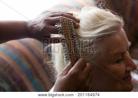 Cropped hands of doctor combing hair of female patient in retirement home