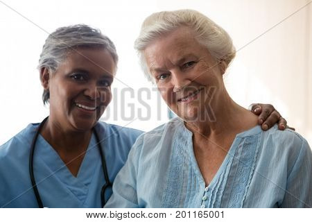 Portrait of smiling nurse and senior woman standing in nursing home