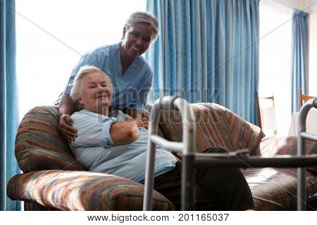 Portrait of smiling nurse with senior woman at sofa in nursing home