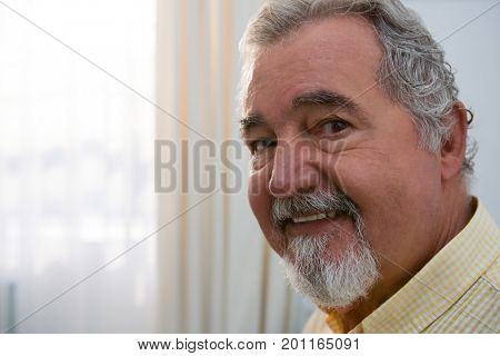 Close up portrait of happy senior man in retirement home