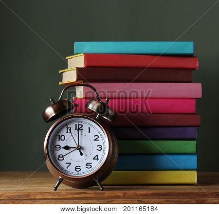 Stack of books in colored covers and retro alarm clock bronze color on the table. Books. Back to school. September 1. The teacher's day.