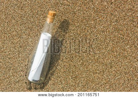 Paper Message in a glass bottle with a cork on the sand. A note on salvation please help