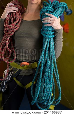 Mid-section of woman with rope in fitness studio