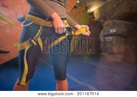 Mid section of woman wearing safety harness in fitness studio