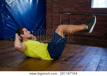 Determined man performing crunches in fitness studio