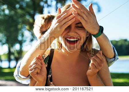 Encounter of happy couple in love outdoors. Lovers are laughing. Attractive girl smiling broadly feeling excited while her boyfriend standing behind her and covering her eyes with his hands
