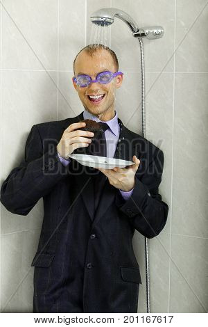 Crazy businessman cooling down, eating a muffin under a shower