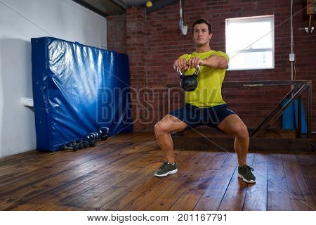 Determined man exercising with kettlebell in fitness studio