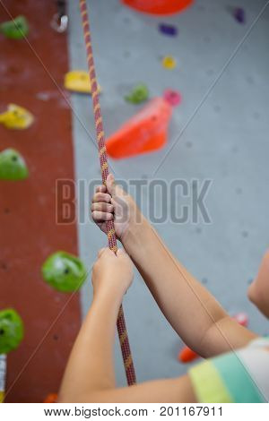 Mid-section of boy practicing rope climbing in fitness studio