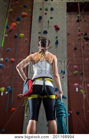 Rear view of woman standing with hand on hip in fitness studio