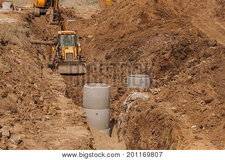 Construction of a new sewerage system. The bulldozer digs a trench for sewer pipes. Construction works