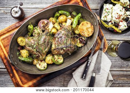 Barbecue leg of lamb with vegetable, potatoes and feta as top view in a casserole