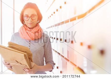 Portrait of creative businesswoman holding envelopes in locker room at office