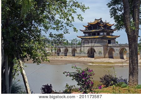 Ancient Stone, segmental arch Bridge with two Three tier Defensive Forts. Ancient, historical Han Dynasty, circa 1100 AD, Shuanglongqiao Double Dragon Bridge , Jianshui, Yunnan, China.
