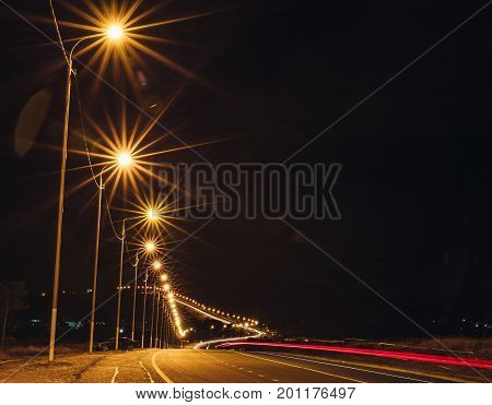 Night road with lanterns in the form of a curve, tracers glowing from the headlights, long exposure, copy space
