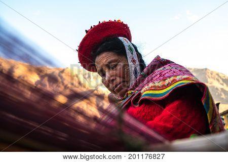 Peruvian woman weaving colorful alpaca wool in Peru