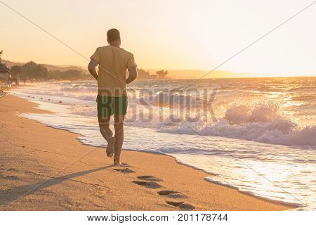Rear view of young jogger running on beach at sunset over sea