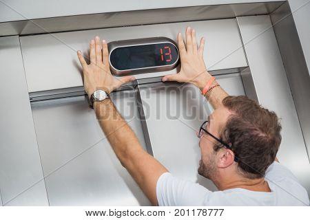 Man is afraid of number thirteen on elevator display.