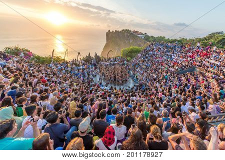 Bali, Indonesia - August 24, 2017: Tourists watch traditional Balinese Kecak Dance at Uluwatu Temple on Bali, Indonesia.  Kecak Dance at Uluwatu Temple on Bali is very popular cultural show on Bali.