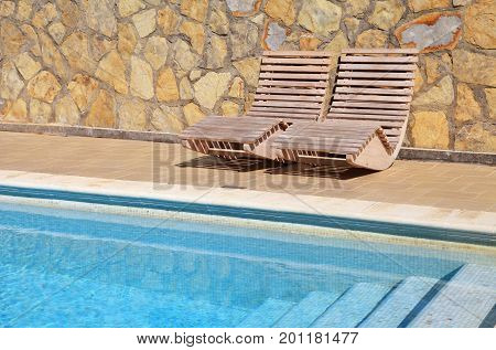 Outdoor wood sun beds near swimming pool on summer resort terrace