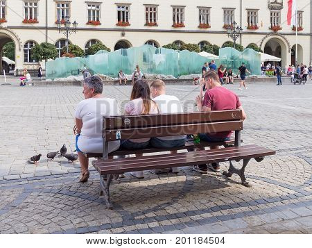 WROCLAW POLAND - AUGUST 14 2017: Tourists On A Bench At Rynek Market Square In Wroclaw