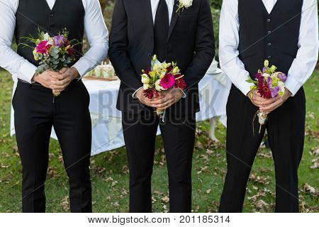 Mid-section of bridegroom and best man standing with bouquet of flowers in garden